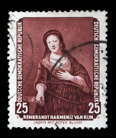 famous paintings: Stamp printed in DDR shows the painting Saskia with red flower, by Rembrandt, from the series Famous Paintings from Dresden Gallery, circa 1957.