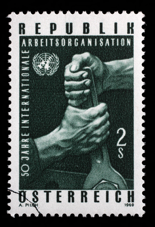 un used: Stamp printed in the Austria shows Hands Holding Wrench, and UN Emblem, 50th Anniversary of ILO, circa 1969