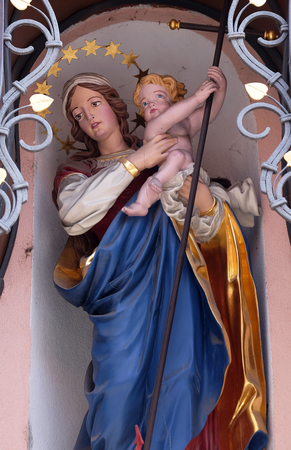 preach: Virgin Mary with baby Jesus, statue on the house facade in Ljubljana, Slovenia