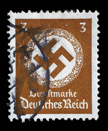 swastika: Stamp printed in Germany shows the Swastika in an oak wreath, circa 1943.