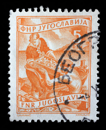 Stamp printed in Yugoslavia shows as woman helps a fisherman unload fish, domestic economy Series, circa 1952