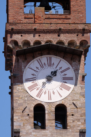 numeros romanos: Torre del Reloj, Campana de Piedra Torre (campanario) rematado con arco de ladrillo y el reloj con números romanos en Lucca, Italia Foto de archivo