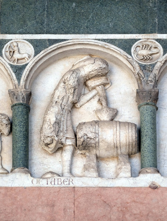 bass relief: October, detail of the bas-relief representing the Labor of the months of the year, portal of the Cathedral of St Martin in Lucca, Italy Stock Photo