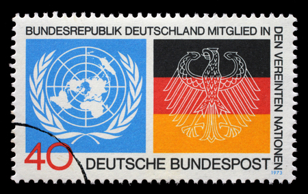 un used: Stamp printed in the Germany shows Emblems from UN and German Flags, Germanys admission to the UN, circa 1973