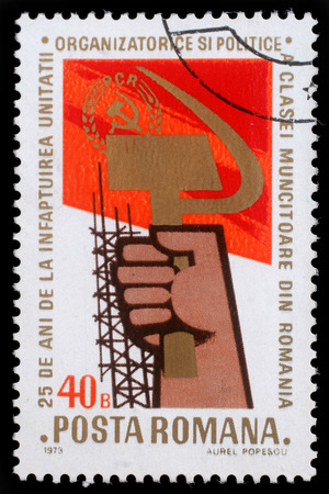 communistic: Stamp printed in Romania showing a hand holding sickle and hammer, circa 1973