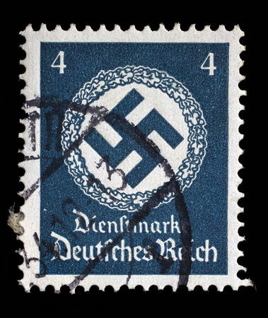 swastika: Stamp printed in Germany shows the Swastika in an oak wreath, circa 1942.