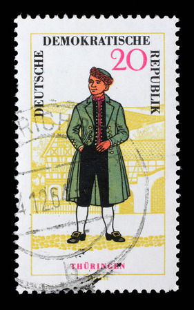 east germany: Stamp printed in East Germany shows regional costume of Thuringen. East Germany, circa 1966