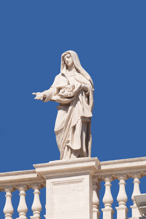 St. Elizabeth of Portugal, fragment of colonnade of St. Peters Basilica. Papal Basilica of St. Peter in Vatican - the world largest church, is the center of Christianity in Rome, Italy
