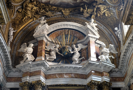 Angels holding a globe with golden rays, and initials IMAS for the names Jesus and Maria, main altar in church Gesu e Maria in Rome, Italy Editorial