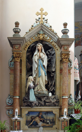 Our Lady of Lurdes staue on the altar in Parish Church of Saint Nicholas in Gusce, Croatia Stock Photo