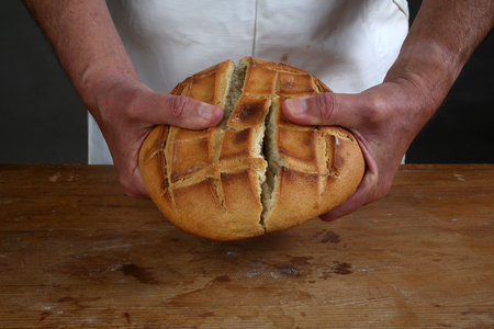 Breaking of a fresh loaf of Eucharistic bread in Zagreb, Croatia