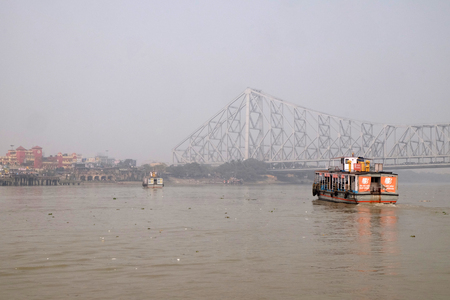 Ferry boat crosses the Hooghly River nearby the Howrah Bridge in Kolkata. To use the ferry is easy, fast and cheap way how to cross the Hooghly River.