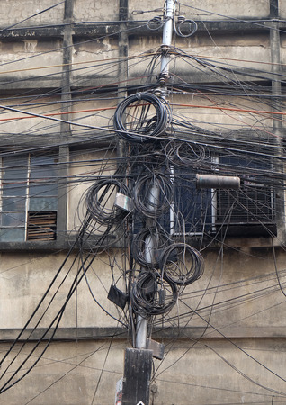 The chaos of cables and wires in Kolkata. Uncovered optical fiber technology open air outdoors in Asian cities.