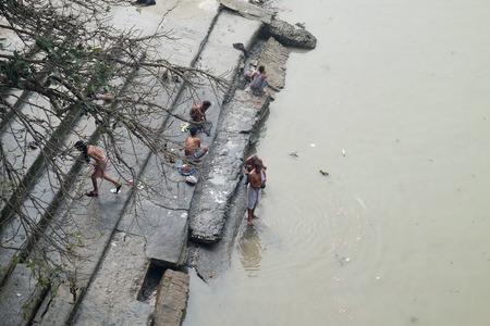 People bathing in river Hooghly under the busy Howrah bridge in Kolkata