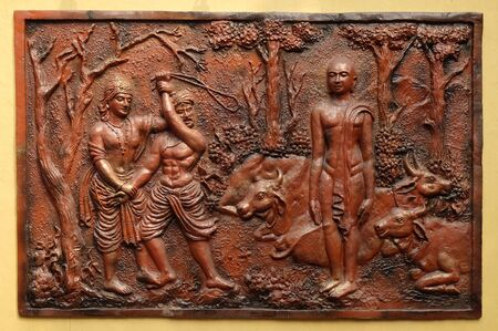 Indra prevents an ignorant cowherd from assaulting Bhagavan Mahavira, Street bas relief on the wall of Jain Temple (also called Parshwanath Temple) in Kolkata, West Bengal, India
