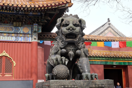 Bronze imperial lion at the gate of Lama Temple Yonghe Lamasery. It is one of the largest and most important Tibetan Buddhist monasteries in the world in Beijing, China