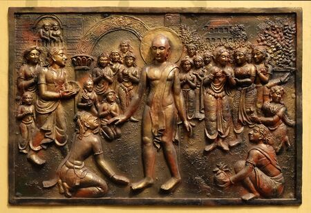 Bhagavan Mahaviras waling tour is beset with pleasant and painful distractions, Street bas relief on the wall of Jain Temple (also called Parshwanath Temple) in Kolkata, West Bengal, India Stock Photo