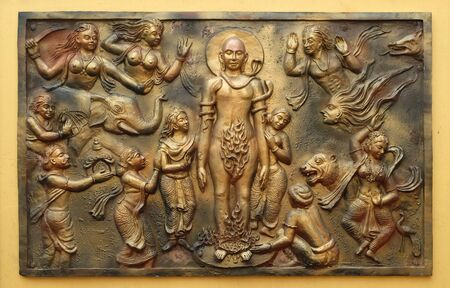 Jealous god Sangama tests Mahaviras enderance and, courage by twenty severe tests: Mahavira is victorius, Street bas relief on the wall of Jain Temple (also called Parshwanath Temple) in Kolkata, West Bengal, India Stock Photo