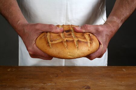 Breaking of a fresh loaf of Eucharistic bread