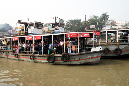 Ferry boat crosses the Hooghly River nearby the Howrah Bridge in Kolkata on February 10, 2016. To use the ferry is easy, fast and cheap way how to cross the Hooghly River. Editorial