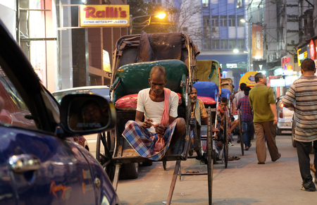 A hand rickshaw puller waits for passengers in his rickshaw in Kolkata on February 10, 2016.