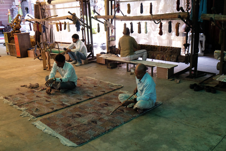 Workers in a hand made carpet cooperative in Jaipur finish carpets in Jaipur, Rajasthan, India on February 16, 2016. Editorial