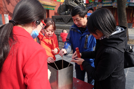Worshippers holding incense sticks pray at Yonghegong Lama Temple in Beijing, China