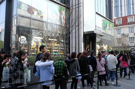 Teenagers waiting in line to enter the Line Friends cafe and shop in Shanghai, China