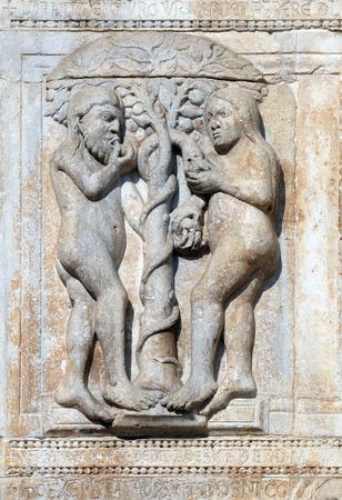Adam et Eve mangent le fruit de l'arbre interdit, soulagement médiéval sur la façade de la basilique de San Zeno à Vérone, Italie Banque d'images