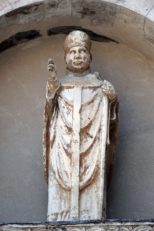 Relief in the lunette depicting the holy bishop, portal of Santa Maria Forisportam church in Lucca, Tuscany, Italy