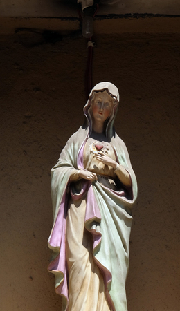 Statue of the Virgin Mary over the entrance door to the house in Lucca, Tuscany, Italy