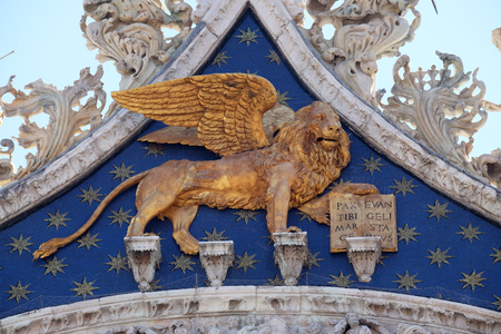 Statue golden winged lion, symbol of Venice on the Basilica of St. Mark on Piazza San Marco, Venice, Italy