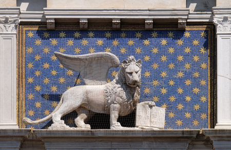 The statue of the winged lion on the St Mark`s Clock tower Torre dell`Orologio on Piazza San Marco, Venice, Italy