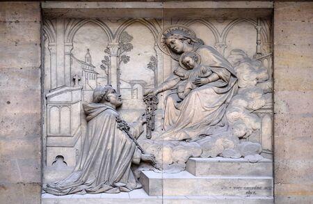 Maagd die de rozenkrans geeft aan Sint Dominicus, door Theodore Charles Gruyere, reliëf op het portaal van Sint Thomas van Aquino in Parijs, Frankrijk Stockfoto