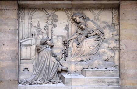 Virgin giving the Rosary to Saint Dominic, by Theodore Charles Gruyere, relief on the portal of Saint Thomas Aquinas in Paris, France Reklamní fotografie