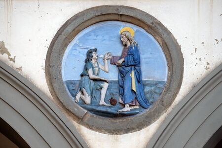 St. Paul healing a sick man. Glazed terracotta tondo by Andrea della Robbia, located between two arches of the old Ospedale di San Paolo, in Florence, Italy.