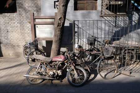 Bicycle and Motorbike in front of a courtyard door in Beijing hutong, China
