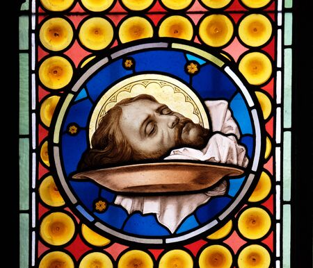 The head of Saint John the Baptist, stained glass window in Basilica of Saint Sylvester the First (San Silvestro in Capite) in Rome, Italy