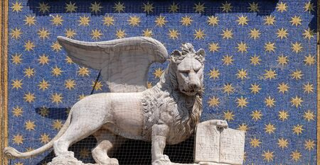 Statue of the winged lion on the St Mark`s Clock tower Torre dell`Orologio on Piazza San Marco, Venice, Italy