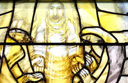 God begins salvation in this world through His Son Jesus Christ, detail of stained glass window by Sieger Koder in St. John church in Piflas, Germany 新聞圖片