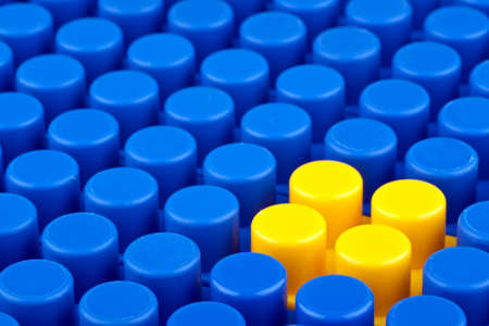 In the picture a bunch of blue plastic blocks and one yellow  They are not legos