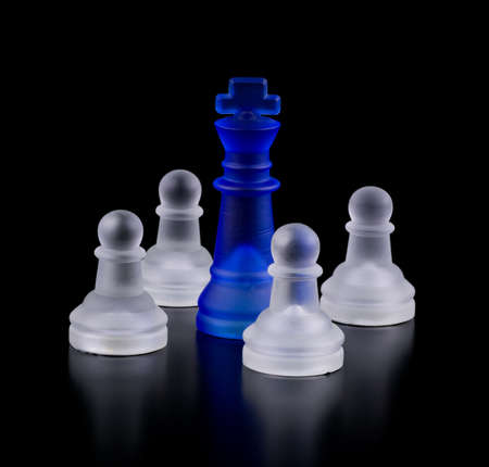 Blue captive king. Chess on a black background. Stock Photo