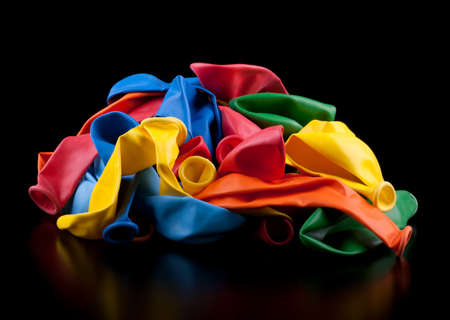 Heap of colorful empty balloons, isolated on black Stock Photo