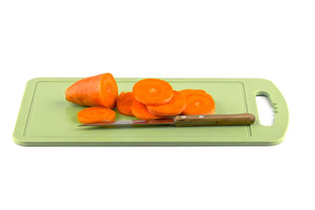 Sliced carrots on a board with a knife.