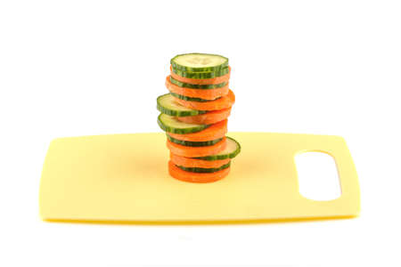Sliced carrots and cucumber on the board.