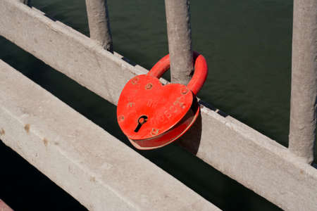 Red metal lock on the grill. Stock Photo