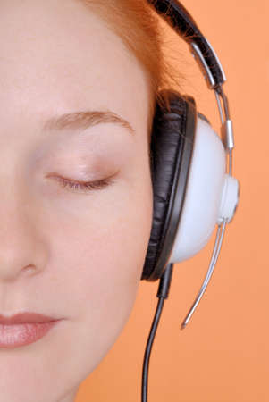 pacification: Redhead young woman in headphones. Part of the face, close-up