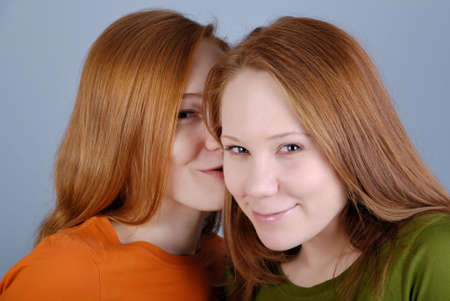 secretive: Two redhead young woman are secretive and smile