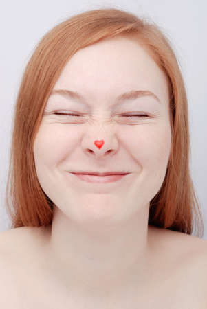 Redhead young woman with heart on nose Stock Photo