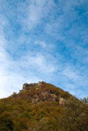 Mountain top under the blue sky with clouds